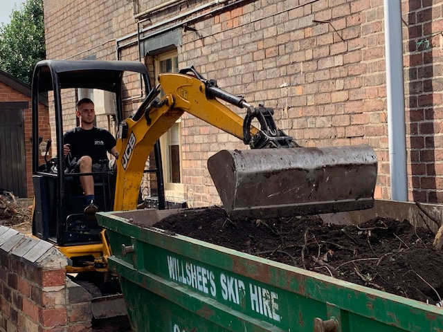 Mini Digger Hire Derby Mini digger filling skip with garden with soil